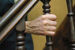 Ältere Frau hält sich am Treppengeländer fest