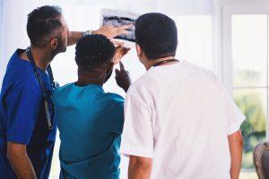 Foto von EVG photos von Pexels. Gezeigt werden 3 Ärzte, die sich ein Röntgenbild anschauen.