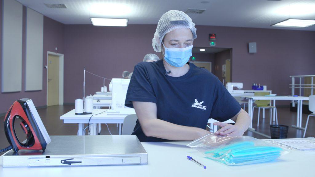 Eine Mitarbeiterin verpackt die frisch genähten Masken