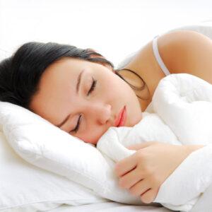 Das Foto zeigt eine Frau, die im Bett liegt und schläft. Foto: obx-medizindirekt